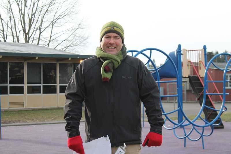 CONNECTION PHOTO: HANNAH RANK - Paul Higgins, co-chair of the Rieke Elementary playground committee, stands in front of the school's existing playground structure. His committee wants to expand to draw in the larger community.