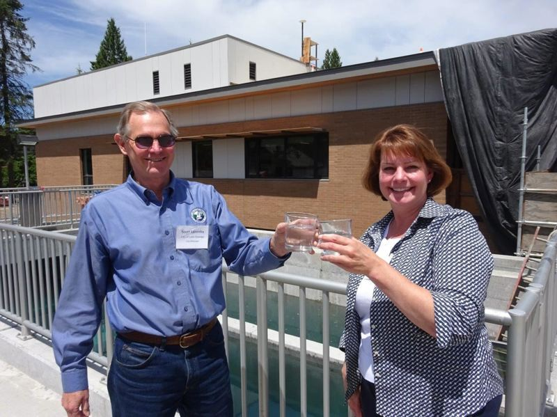 FILE - Lake Oswego and Tigard city managers Scott Lazenby and Marty Wine celebrate the completion of the joint water system with glasses of drinking water last July.
