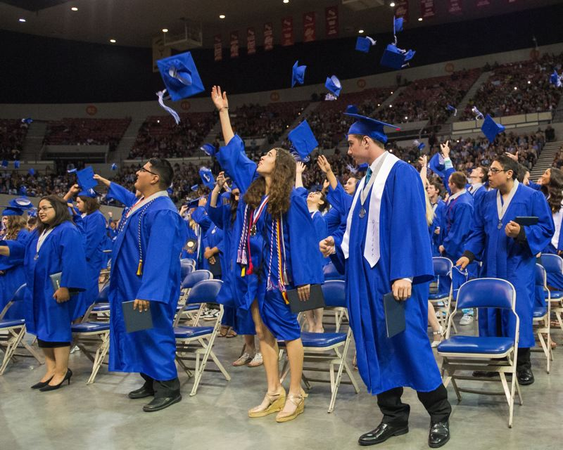 FILE PHOTO - Gresham High School 2016 graduates throw their caps in the air at graduation time. The Gresham-Barlow School district has improved its graduation rate 16 percentage points over the past five years.