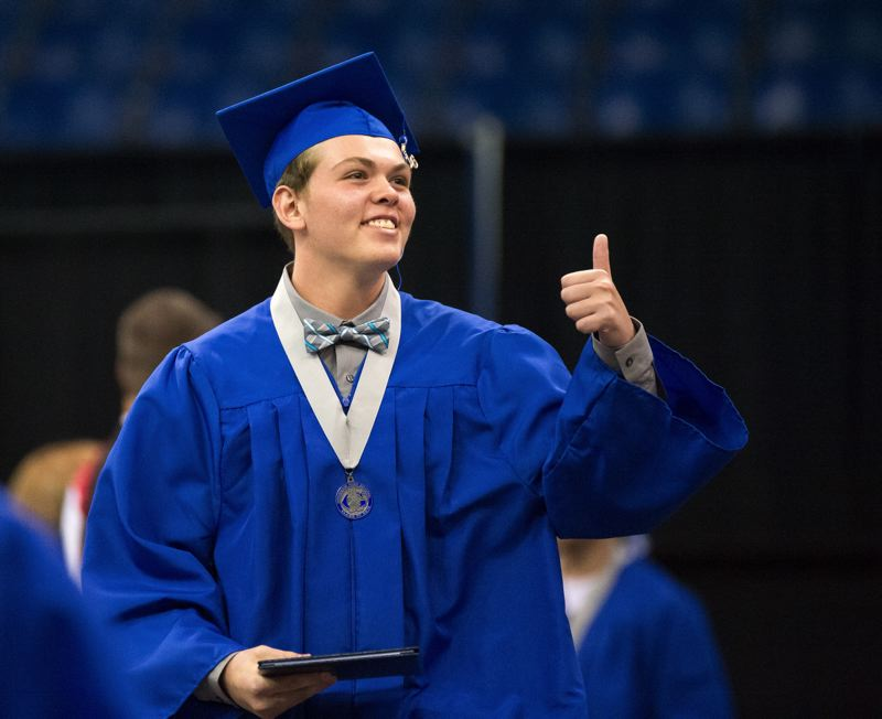 FILE PHOTO - A Gresham High School 2016 graduate gives the crowd a thumbs up at a graduation ceremony. GHS improved its 2016 graduation rate to 78.4 percent from 76.6 percent a year earlier, besting the state as a whole.