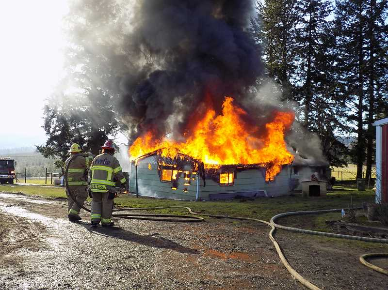 GAZETTE PHOTO: RAY PITZ  - This garage and adjacent home were believed to have been built in the 1950s. The property owners allowed firefighters to train at the site and remove the structure by letting it burn down.
