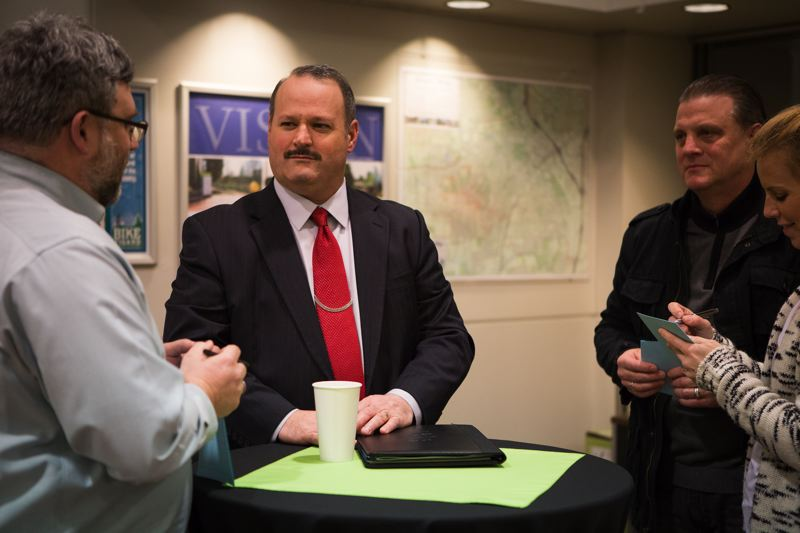 TIMES PHOTO: ADAM WICKHAM - Sherwood Police Chief Jeff Groth, on the shortlist to become Tigard's next police chief, listens to Tigard City Council President Jason Snider as residents take notes.