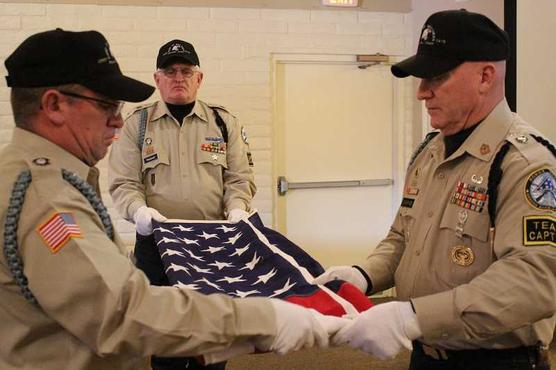 JASON CHANEY - From left, Donald Davis, Clyde Peacock and Dan Swearingen practice folding the American flag prior to a funeral service.