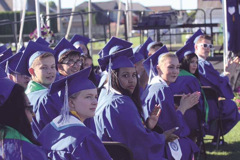 INDEPENDENT FILE PHOTO - Graduates of the class of 2016 at Woodburn High School applaud family and friends who witnessed their commencement in June 2016. The class saw a slight decline in graduation rates from the previous year.