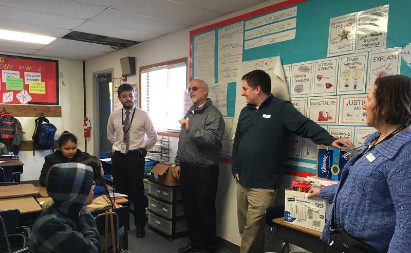 LINDSAY KEEFER - Kiwanis member Mark Wilk (center) explains what Kiwanis is to a classroom at Washington Elementary School while Principal Juan Larios (left) and Kiwanis members Michael Nelson and Julie Moore look on.