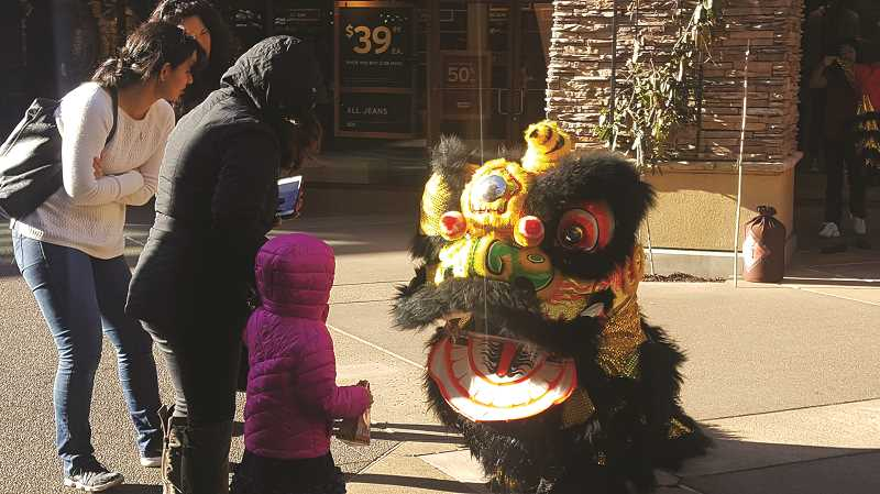 COURTESY PHOTO: WPO - Shoppers pause from their day of shopping Friday to enjoy the International Lion Dance, led by Michael Choi, at Woodburn Premium Outlets, which celebrated the Chinese New Year over the weekend with lion and dragon dances and gold coin giveaways.