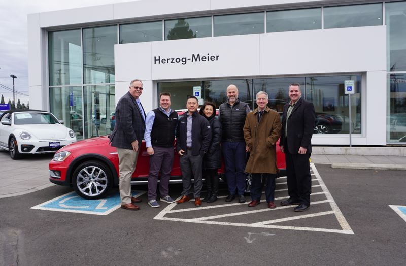 PAMPLIN MEDIA GROUP: JEFF ZURSCHMEIDE - Chris Meier and Tom Herzog from Herzog-Meier Volkswagen, along with Greg Remensperger and Jeff Fishback of the Metro Portland New Car Dealers Assocation and Portland Tribune President and Publisher Mark Garber gather to present Henry Cha and Paylee Herr with the keys to their new 2017 Volkswagen Golf Alltrack SEL. (L-R: Remensperger, Herzog, Cha, Herr, Meier, Garber andJeff Fishback.)