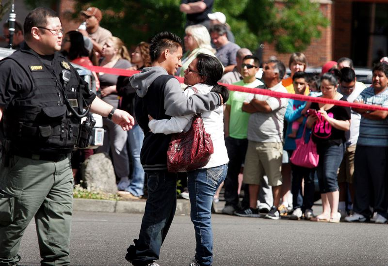 FILE PHOTO - A Reynolds High School student is reunited with a family member at the Wood Village Town Center after a shooting at the school on the morning of June 10, 2014. Students were bused from the campus to the shopping mall parking lot for the reunification with their parents.