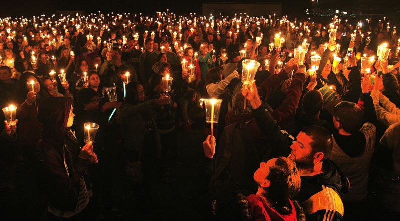 FILE PHOTO - Community members attending the candlelight vigil at Reynolds High School Tuesday night hold their candles up in remembrance of the two students who died violently within the gym nearby.