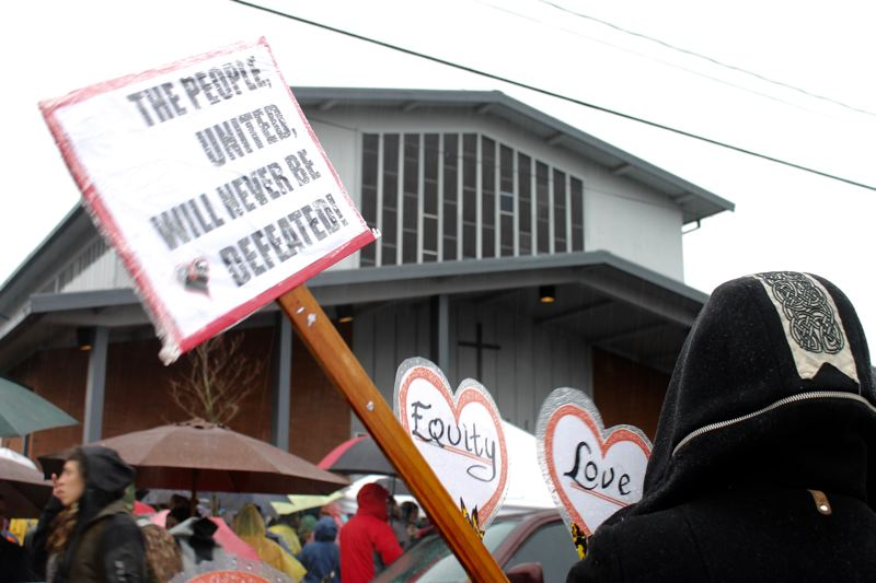 TRIBUNE PHOTO: LYNDSEY HEWITT - About 200 people carried signs and stood outside St. Peter Catholic Church Sunday, Feb. 5, after a racial incident Jan. 29.