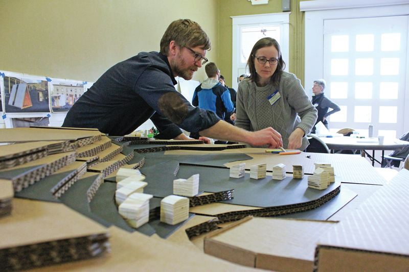 TRIBUNE PHOTO: LYNDSEY HEWITT - Todd Ferry, research associate for the Center for Public Interest Design at Portland State University, which helped physically build the pods, looked at a model of the Kenton site at a recent design charrette.
