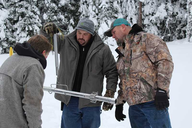 JASON CHANEY - Ochoco Irrigation District Manager Russ Rhoden (left) and employees Ryan Middaugh (center) and Justin McKinney check snow depth near Walton Lake and weigh the snow to determine its water content.