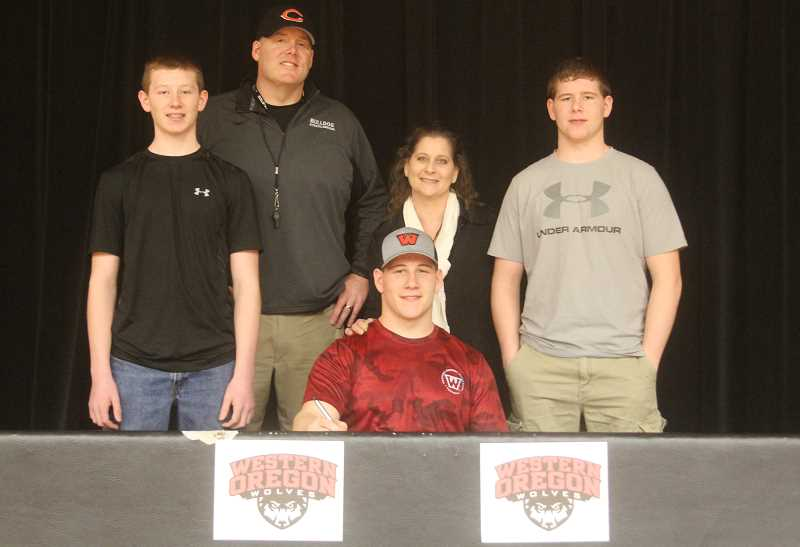 WILL DENNER/MADRAS PIONEER - Clockwise from top left, Mack Little's father and coach, Shea, mother, Naomi, and younger brothers, Cole and Brody, gathered in Culver's gym Wednesday as Little signed his National Letter of Intent with WOU.