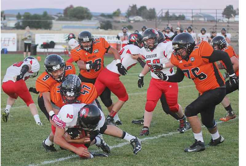 JEFF WILSON/MADRAS PIONEER - Culver defenders Mack Little (47) and Marco Retano (9) bring a Santiam runner down in a September 2015  game. Little said he prefers to play defense, where he can hit people, but would play any position where playing time is available.
