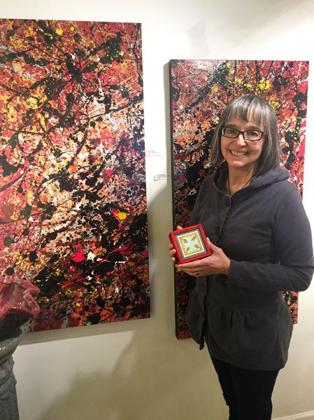 ESTACADA NEWS PHOTO: EMILY LINDSTRAND - Nolene Triska holds her piece Tree Box while standing in front of Carol Pulvermachers piece Crimson Sisters. The works are a part of the Spiral Gallerys February group show, Red.