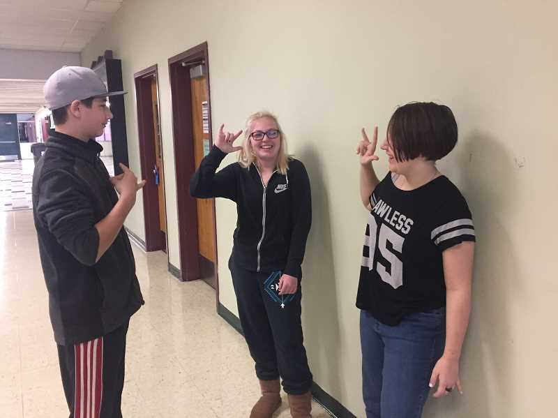 ESTACADA NEWS PHOTO: EMILY LINDSTRAND - Students Josh Townsend, Bailey Bard and KaeLeah Dodd practice the signs they've learned in the ASL I class at Estacada High School.