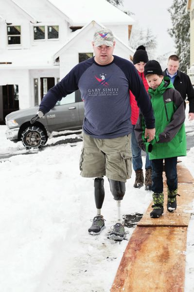 COURTESY OF THE GARY SINISE FOUNDATION - Retired U.S. Army Sgt. Wade Mitcheltree navigates through the snow on his prosthetic legs at the site where his house is being built on Inez Street in Tigard.