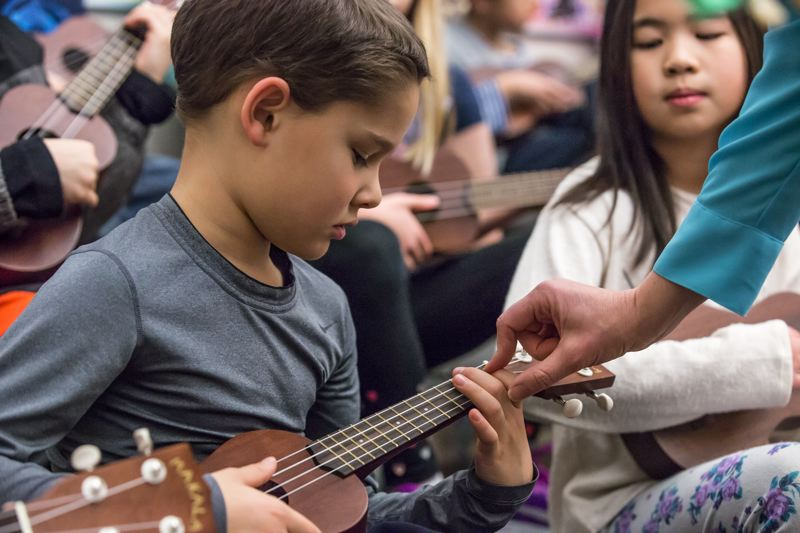 TIMES PHOTO: JONATHAN HOUSE - Alberta Rider Elementary School student Gabe Barton gets a little help with playing his ukulele from music teacher Emily Kelchner Lee.
