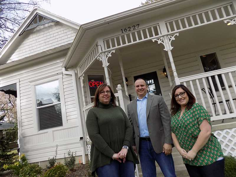GAZETTE PHOTO: RAY PITZ - Gardner Team Real Estate employee Jennifer Roger, joins Jason Gardner and Amber Gardner outside the 2,000-square-foot Queen Anne-style Victorian home the Gardners purchased several years ago for use as office space.