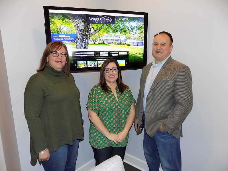 GAZETTE PHOTO: RAY PITZ - Gardner Team Real Estate employee Jennifer Roger, joins Amber and Jason Gardneer in front of one of three Apple TVs the Gardners have in their new home office on First Street.