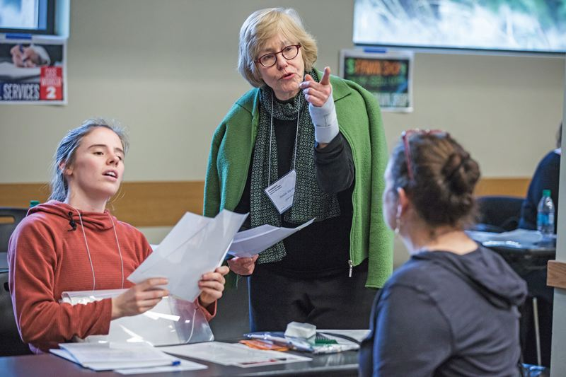 PORTLAND TRIBUNE: JONATHAN HOUSE - Carol Turner and Emily Wilson play social service workers helping a client during a poverty simulation at Portland State.
