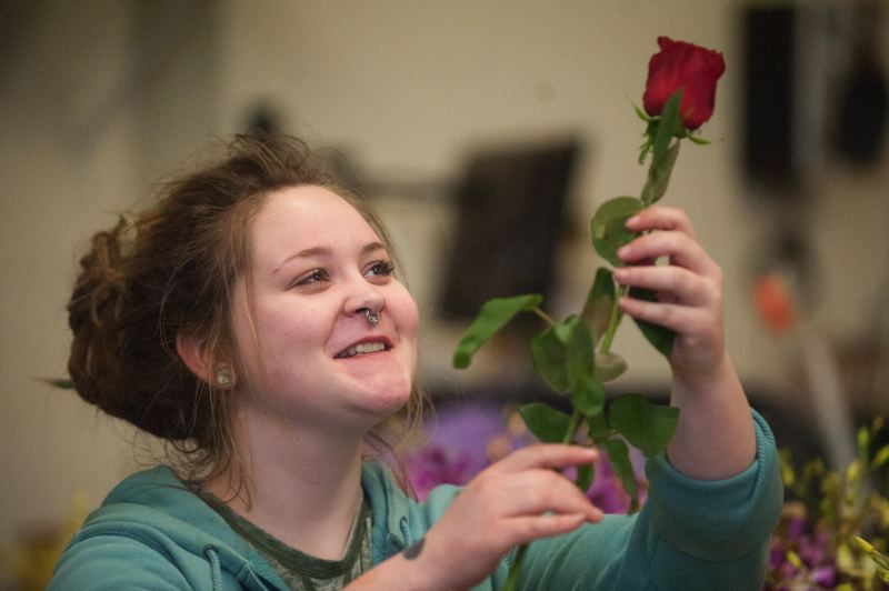 OUTLOOK PHOTO: JOSH KULLA - Nancy's Flowers staffer Bethany Ryan inspects a long-stemmed rose Monday, one day before Valentine's Day.