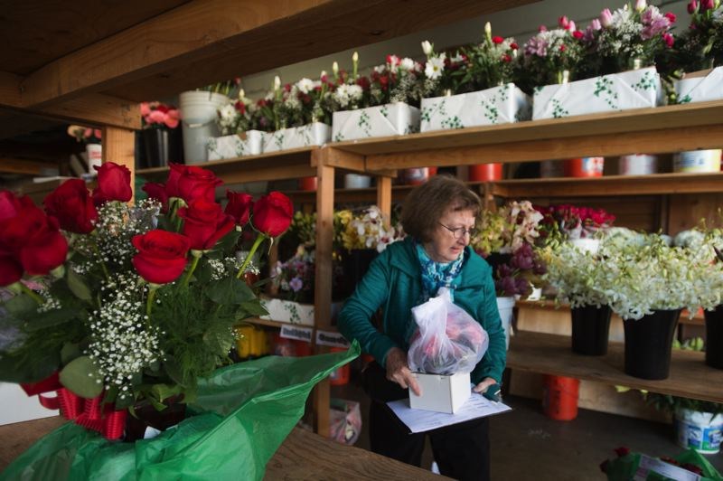 OUTLOOK PHOTO: JOSH KULLA - A volunteer picks up a bouquet of Valentine's Day flowers from Nancy's Flowers in Gresham. A team of volunteers from Meals on Wheels and other local groups delivered hundreds of bouquets to area residents for the holiday.