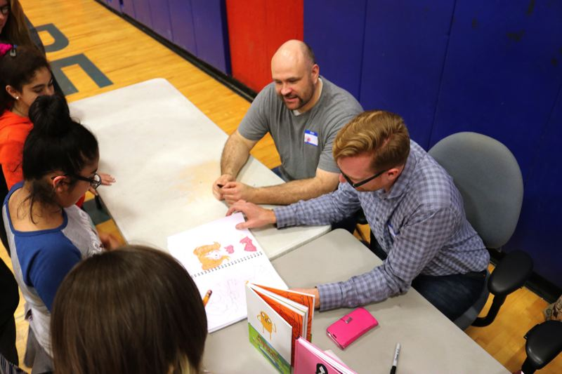 CONTRIBUTED PHOTO - Authors Dean Hale and Ryan North check out  student illustrations.