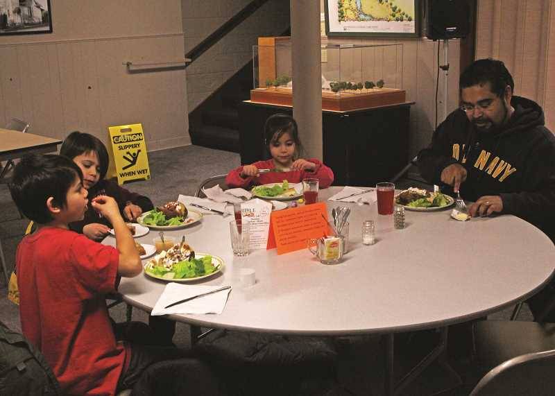 INDEPENDENT PHOTO: JULIA COMNES - (From right) Ulises Rodriguez eats with his children Ismari, Oliver and Anthony. The community dinners have become part of the family's Wednesday routine.