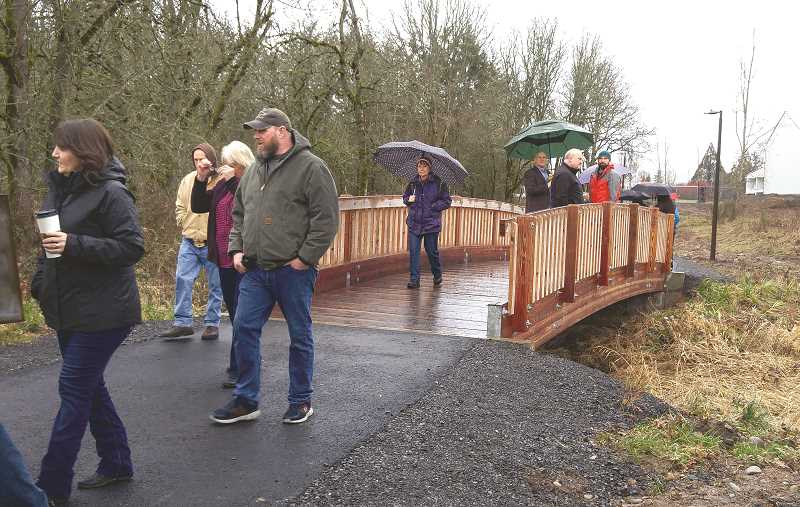 KAREN GRAVES - Some of those attending the ceremony walk through the rain to cross the bridge. Standing on the bridge is L-R, Craig Loughridge, holding the green  umbrella, Neal Lucht, whose company contributed to the project, and  Evan Christoff, PSU School of Engineering.