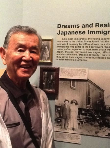 SUBMITTED PHOTO - George Nakata stands in front of a photo depicting first generation Japanese immigrants.