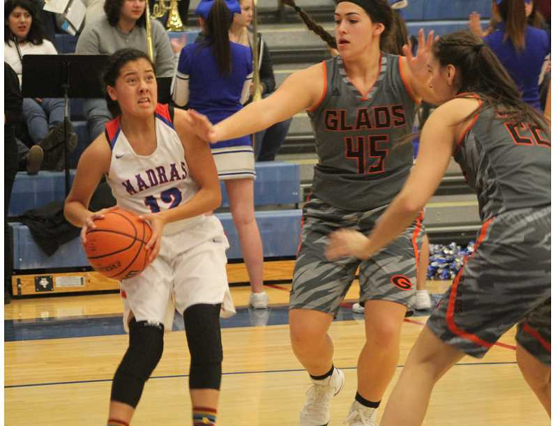 WILL DENNER/MADRAS PIONEER - Madras sophomore Jackie Zamora (left) gathers the ball against Gladstone defenders in the first quarter.