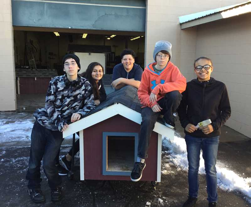 SUBMITTED PHOTO - MHS students Tyler Sharkey, left, Tazman Loosli, Justice Nelson, Austin Taylor, and Sha'Rita Johns pose with one of the dog houses they helped build in the construction class.