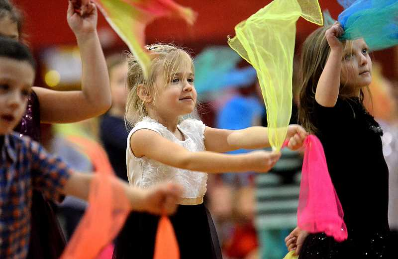 TIDINGS PHOTO: VERN UYETAKE - Victoria Olson, middle, and Melissa Zimmerman, right, perform the 'Never Fully Dressed Without a Smile' scarf dance with the kindergartners.