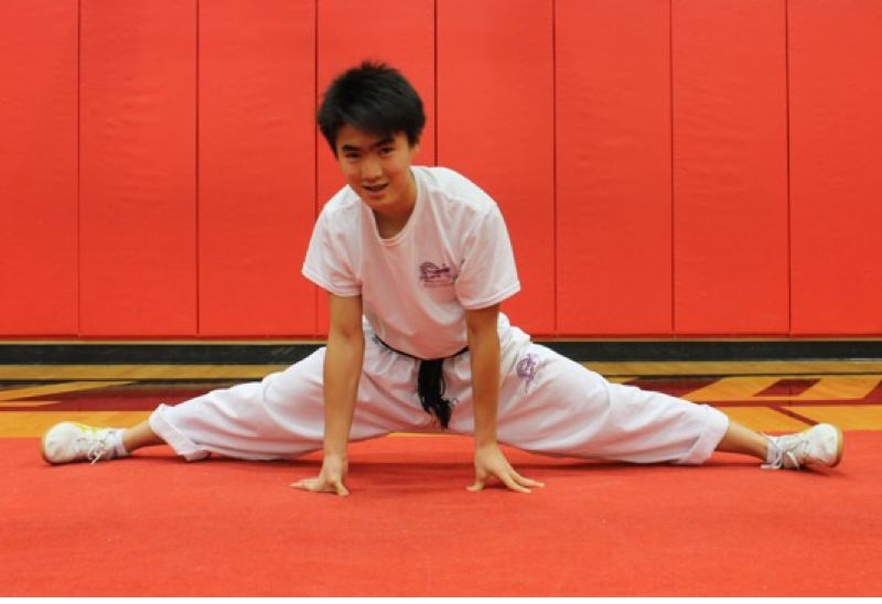 TRIBUNE PHOTO: LYNDSEY HEWITT - Alexander Yu stretches in preparation for wushu practice.