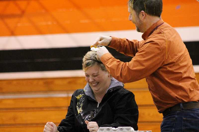 PIONEER PHOTO: CONNER WILLIAMS - Molalla High School language arts teacher John Flavin smashes an egg on fellow language arts teacher Hayley Zeal's head as part of a teacher promise that had each ask the other a question, and if they got it wrong, egg-smashing ensued.