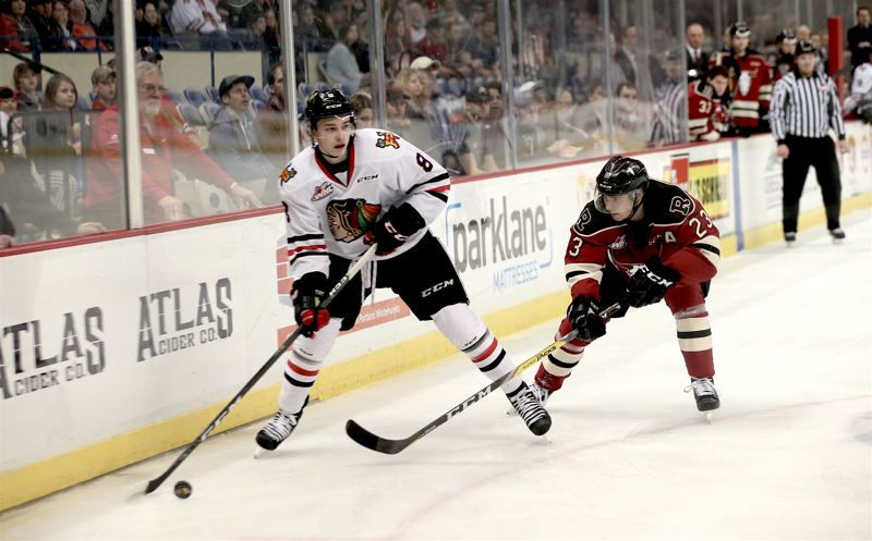 COURTESY: BRYAN HEIM/PORTLAND WINTERHAWKS - Portland Winterhawks forward Cody Glass looks for an open passing lane, keeping the puck away from Red Deer forward Michael Spacek, Friday night at Memorial Coliseum.