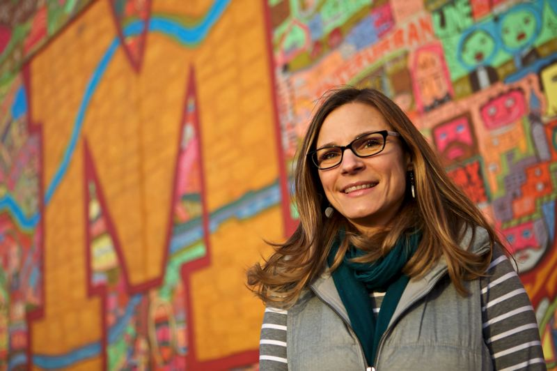 PHOTO BY CRAIG MITCHELLDYER - Kami Aguilar, board president and founder of the fund, stands in front of the iconic mural at Milwaukie High School.