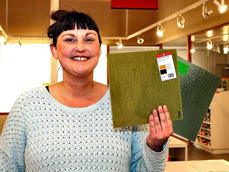 DAVID F. ASHTON - Bullseye Glass Companys Sarah Milliron shows some of their new green glass, made with an ancient process not using chromium - including a sheet of double-rolled opalescent Citronelle.