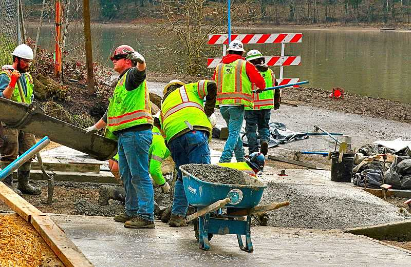 DAVID  F. ASHTON - Workers pour concrete as they complete the sidewalk near the bank of the Willamette River under the new Sellwood Bridge.