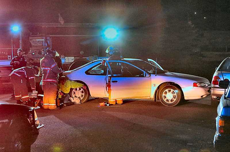 DAVID F. ASHTON - Paramedic/firefighters and police officers spoke with the apparently-impaired driver of the Ford Thunderbird, seated outside his car - after he was involved in a very low-speed bump into a parked car.