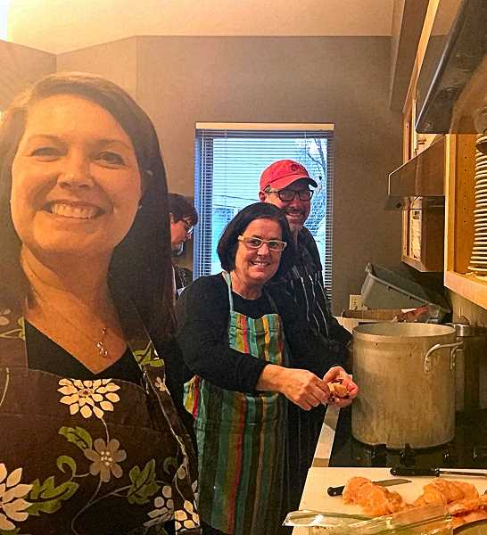 RE/MAX agents Sue Hildreth, Ann Lindsay, and her husband Jeff,  busy in the kitchen at the Willamette Center woman and couples shelter in Westmoreland.
