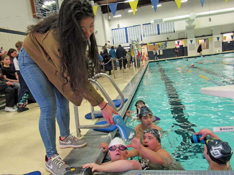 REVIEW PHOTO: JILLIAN DALEY - Jenny Kwon offers Irvin Herrera something to keep him afloat during swim team practice. The students are, from back to front: Hannah Pebley (senior), Jeremy Chen (freshman), Herrera (junior), Megan Schiedler (senior) and George Wadell (sophomore).