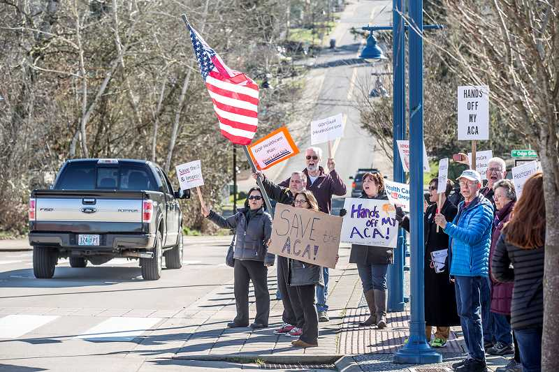 PAMPLIN MEDIA GROUP: JON HOUSE - Protesters waved flags and held pro-Obamacare signs in downtown Sherwood.