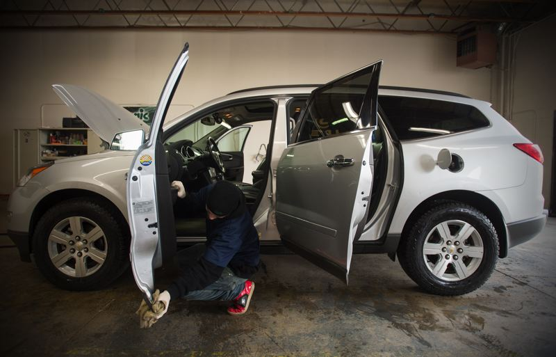 OUTLOOK PHOTO: JOSH KULLA - Auto Bliss employee Jacob Crase wipes down the door of a customer's SUV with a clay-lined cloth that removes dirt, grime and residue from surfaces far more effectively than traditional wash methods.