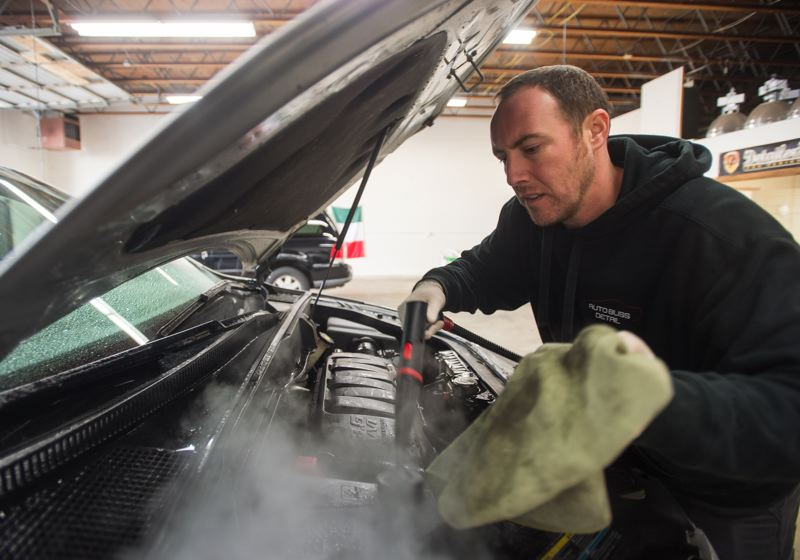 OUTLOOK PHOTO: JOSH KULLA - Phil D'Avanzo steam cleans the engine compartment of a Chevrolet SUV.7.