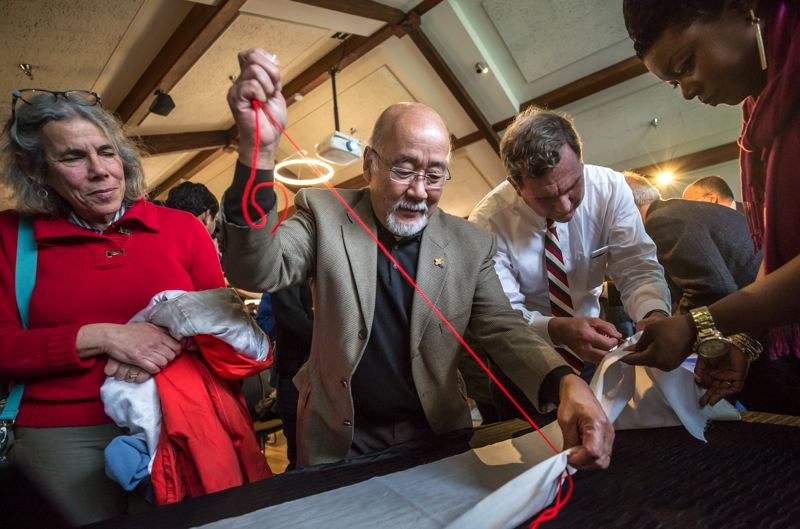 TRIBUNE PHOTO: JONATHAN HOUSE - Portland businessman Sho Dozono creates a thread in a Senninbari tapestry during PCC's Day of Remembrance.