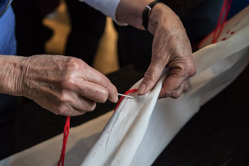 TRIBUNE PHOTO: JONATHAN HOUSE - A Senninbari tapestry is created during Portland Community College's Day of Remembrance. The talisman was carried into battle by Japanese soliders and was adopted by PCC to symbolize the fight against oppression.