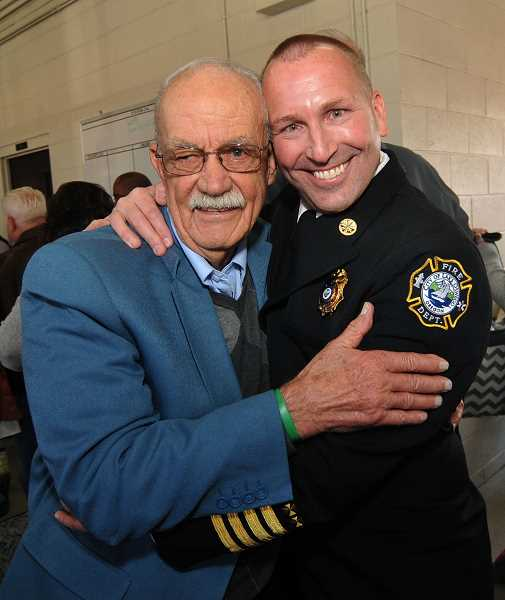 REVIEW PHOTO: VERN UYETAKE - Retired Gaston Fire Chief Ron Hoodenpyl hugs LOFD Assistant Chief David Morris on Saturday. Hoodenpyl, who gave Morris his first paid firefighting job, was a surprise guest at the promotion ceremony.