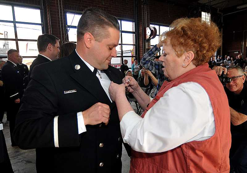 REVIEW PHOTO: VERN UYETAKE - Lt. Paul Lauritzon's new badge is pinned on by his mother Lynn during Saturday's promotion ceremony.
